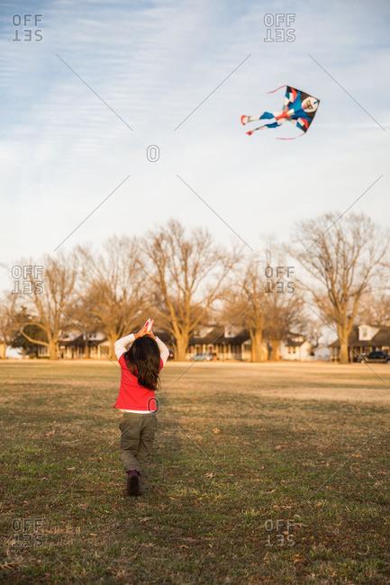 Girl flying kite in meadow