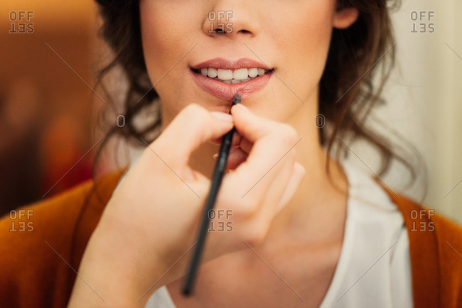 Bride having lip color applied for her wedding