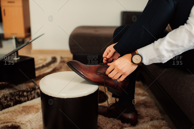 Man tying laces on his brown shoes