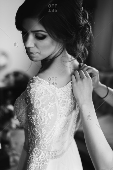 Woman buttoning up the back of a bride's gown