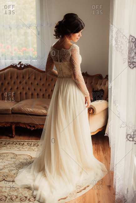 Bride in her wedding gown standing by a window