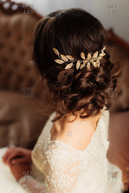 Rear view of bride sitting in her gown on a vintage sofa