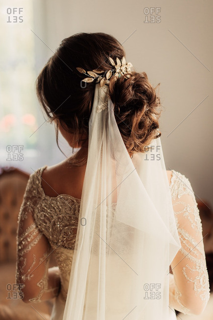 Rear view of bride with veil and gold leaves