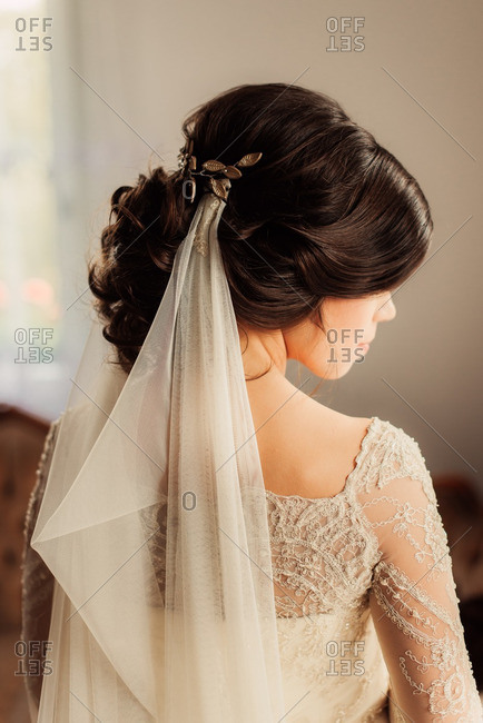 Rear view of bride with veil looking to her side