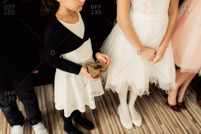 Children at a wedding in formalwear with girl holding rings on a wooden heart