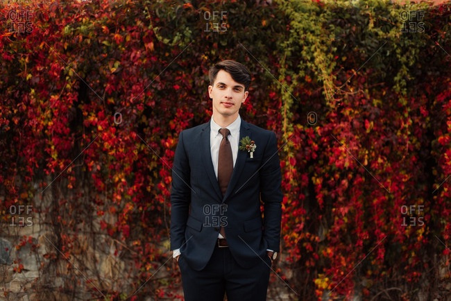 Groom standing by colorful fall vines