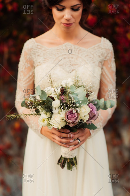 Close up of a bride holding bouquet standing by colorful fall vines