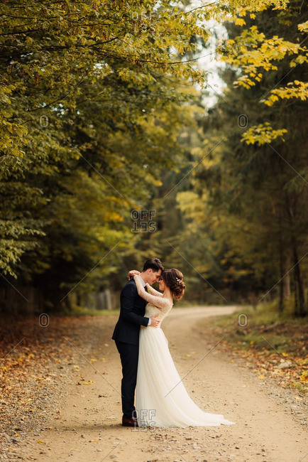Bride and groom embraced on a country road
