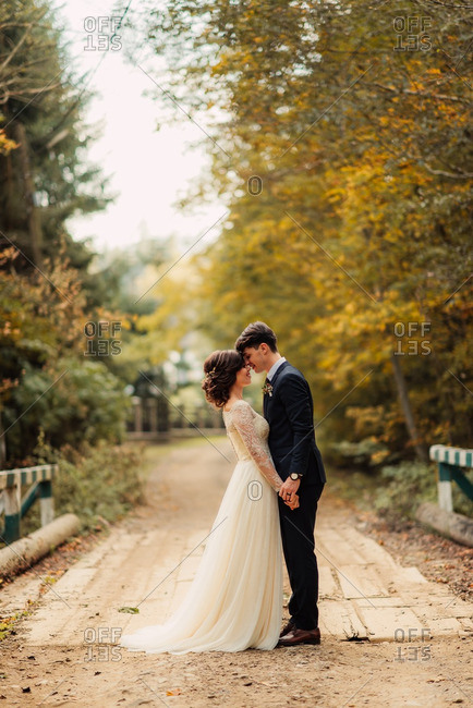 Groom and his bride holding hands face to face on an old wooden bridge