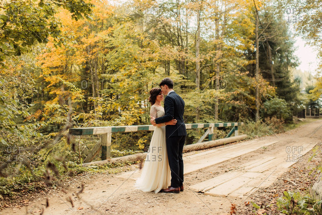 Bride and groom standing face to face on an old wooden bridge