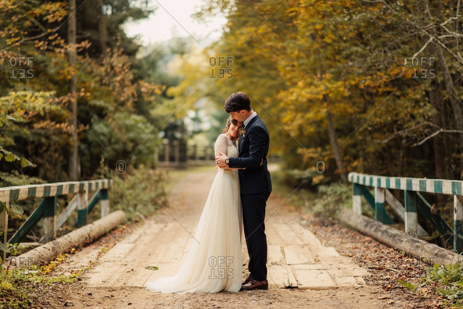 Bride and groom embraced on an old wooden bridge