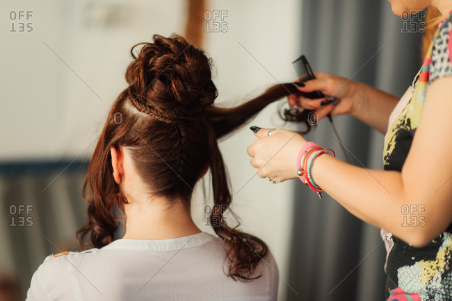 Rear view of brunette bride getting her hair done before her wedding