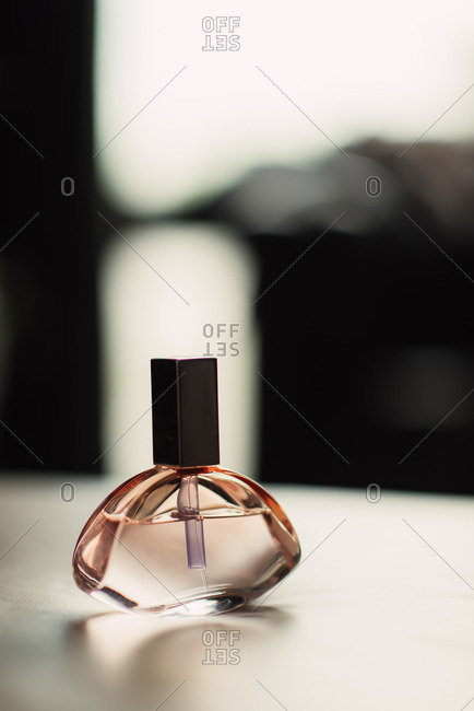 Close up of a rose colored bottle of perfume