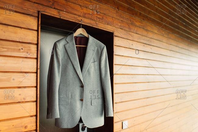 Gray blazer hanging from doorway of a wooden building exterior