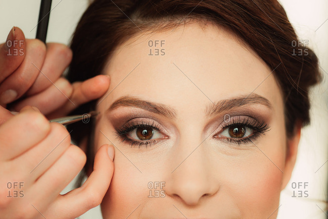 Woman having her eyebrow makeup done for her wedding