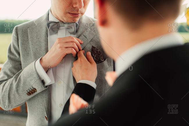 Groomsman helping groom get dressed for his wedding