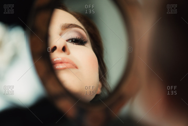 Woman looking in mirror at her makeup before for her wedding