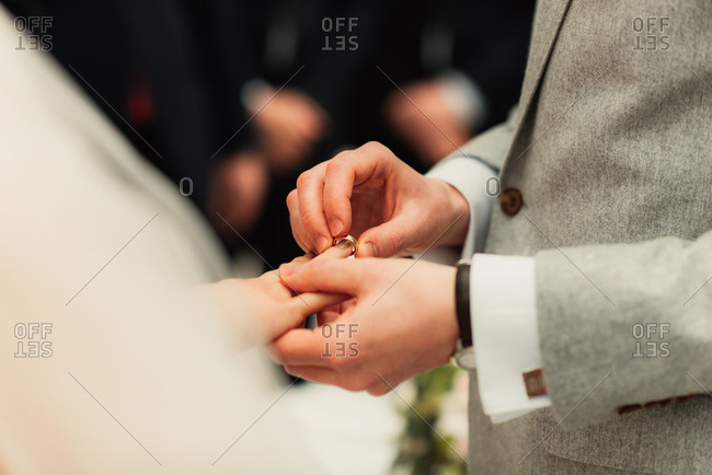 Groom placing ring onto his bride's finger