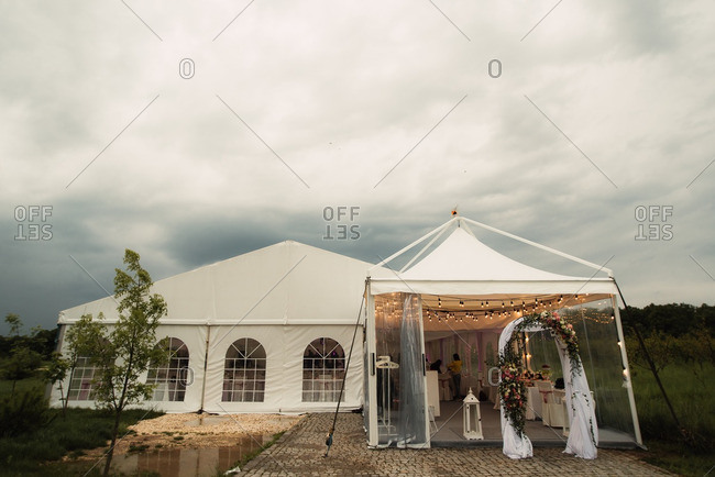 Arbor with flowers in front of a wedding tent