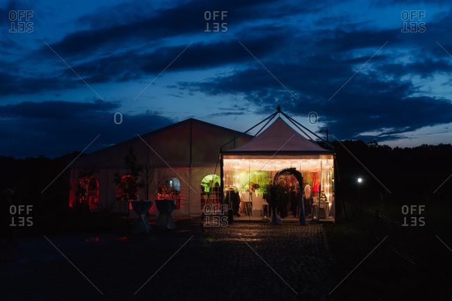 Tent housing a wedding reception at dusk
