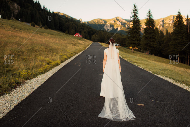 Bride with long veil walking down a paved country road