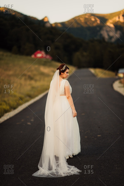 Bride with long veil standing on a paved country road