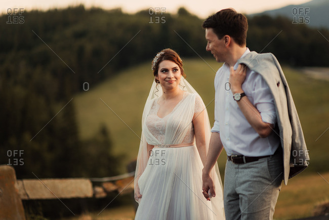 Bride and groom walking hand in hand in the countryside