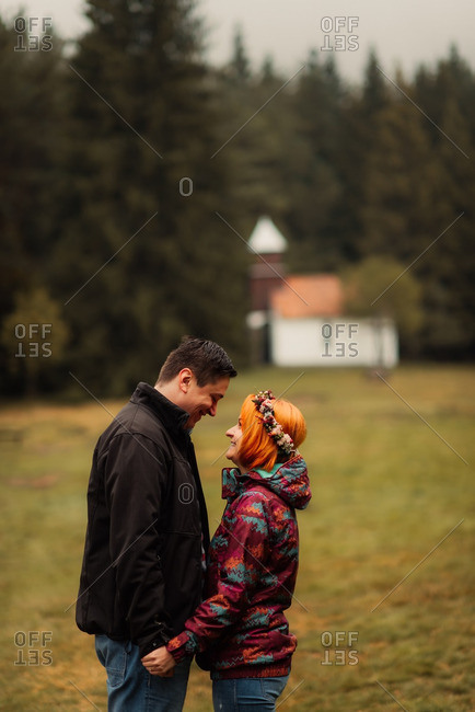 Couple holding hands with quaint church in the background