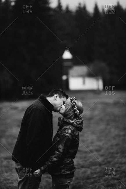 Couple kissing with quaint church in the background