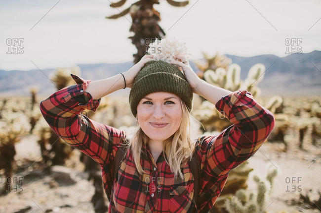 Woman in a plaid shirt and toboggan standing in front of cactus plants