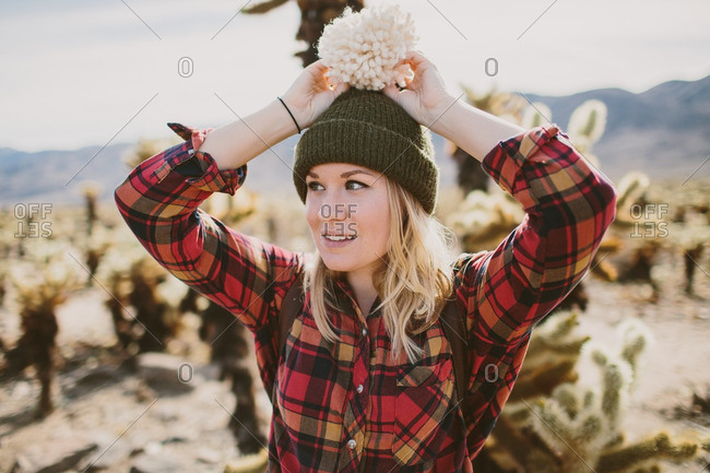 Woman wearing a toboggan standing in front of cactus plants