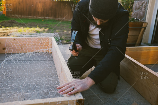 Man attaching chicken wire to a wooden frame
