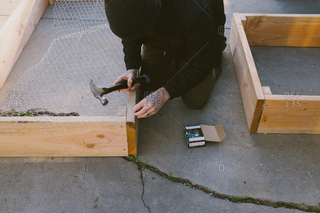 Man attaching chicken wire onto a wooden frame on a patio