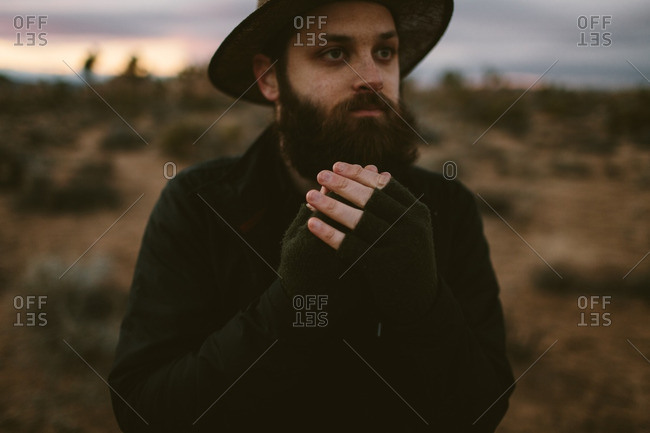 Man in a desert at sunset warming his hands