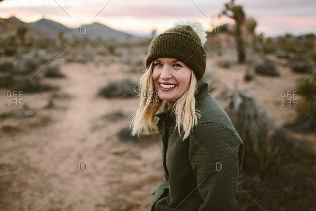 Woman in a toboggan standing in a desert smiling