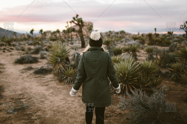 Woman in a toboggan walking among cacti in a desert