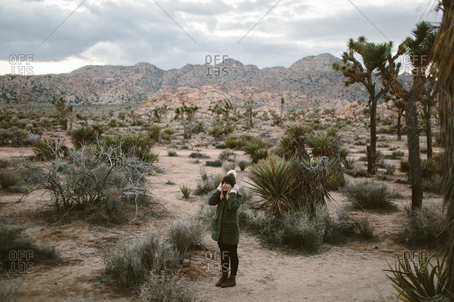 Woman standing in a desert covering her ears to warm them