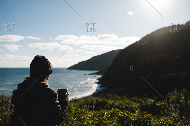 Woman with mug of coffee overlooking sea cliffs