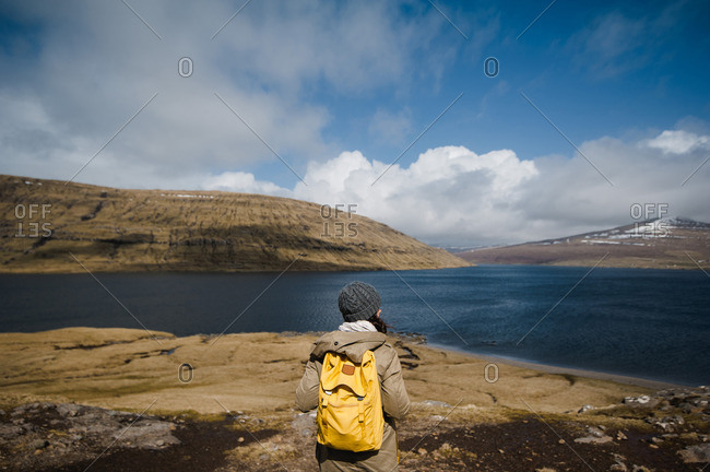 Woman with yellow backpack overlooking mountains and sea