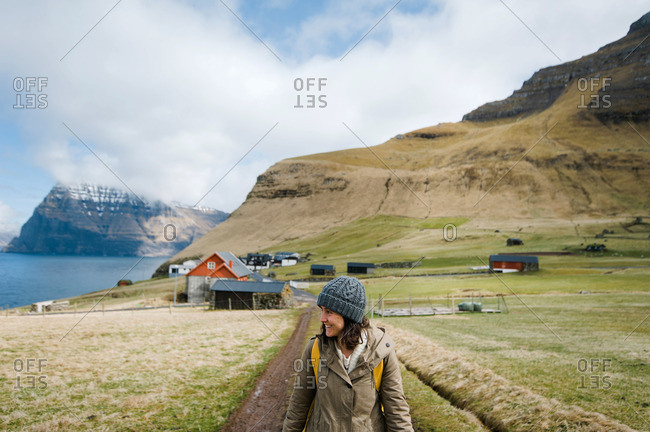 Smiling woman hiking past farm in the Faroe Islands