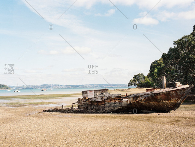 Weathered wooden fishing boat falling apart on a beach