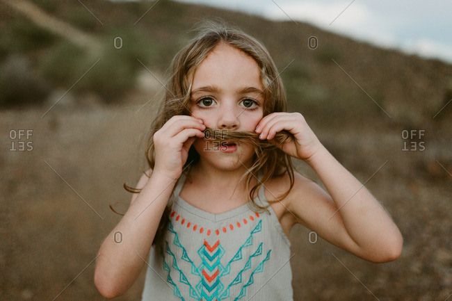 Girl making moustache with her hair