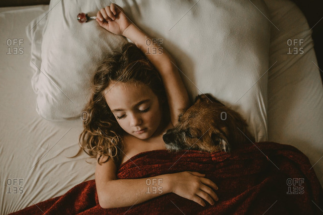 Girl holding sucker napping with dog