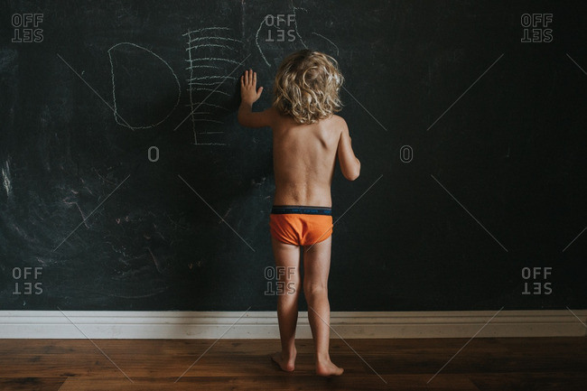 Boy writing on chalkboard wall