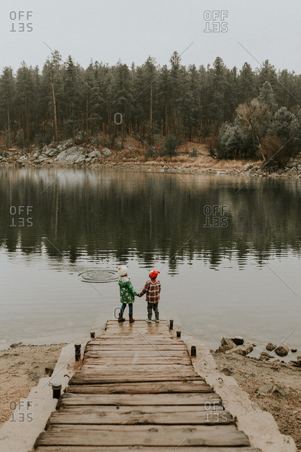 Kids holding hands by lake in cold weather