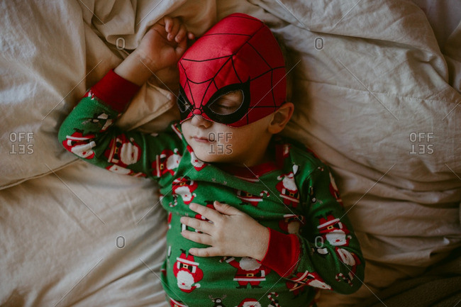 Boy napping in a super hero mask