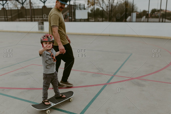 Boy riding skateboard with dad