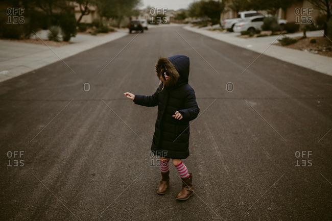 Girl in sunglasses and coat in street