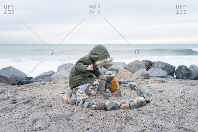 Child playing with rocks on winter beach
