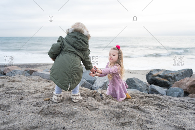 Girls playing on cold beach